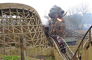 The Wicker Man erupting in flames as a rollercoaster train passes close-by