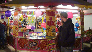 Traditional fun fair games stalls nestle between the thrill rides