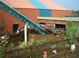 A Colossus train emerges from the ride station