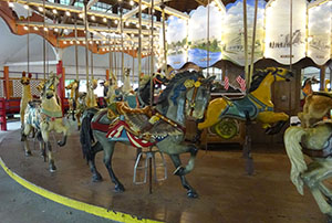 Riders can choose to ride on one of the carousel's varied wooden horses